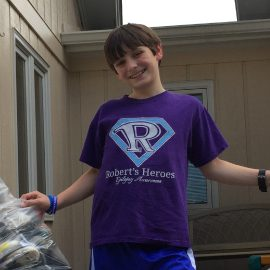 Image of a boy with bags from shoe donations, shoe drive fundraiser